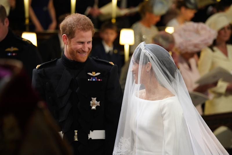 TOPSHOT - Britain's Prince Harry, Duke of Sussex, (L) and US fiancee of Britain's Prince Harry Meghan Markle arrive at the High Altar for their wedding ceremony in St George's Chapel, Windsor Castle, in Windsor, on May 19, 2018. (Photo by Jonathan Brady / POOL / AFP) (Photo credit should read JONATHAN BRADY/AFP via Getty Images)
