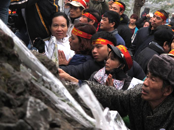 Anti-China protestors lay wreaths at a pagoda in the Vietnamese capital on Sunday, Feb. 16, 2014 to make the 35th anniversary a border war between China and Vietnam. Vietnam is wary of all forms of public protest and often quashes ant-China gatherings (AP Photo/Chris Brummitt)