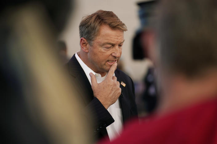 Former U.S. Sen. Dean Heller, center, speaks with the media at an event at Share Village Las Vegas after announcing a bid for governor of Nevada, Monday, Sept. 20, 2021, in Las Vegas. (AP Photo/John Locher)