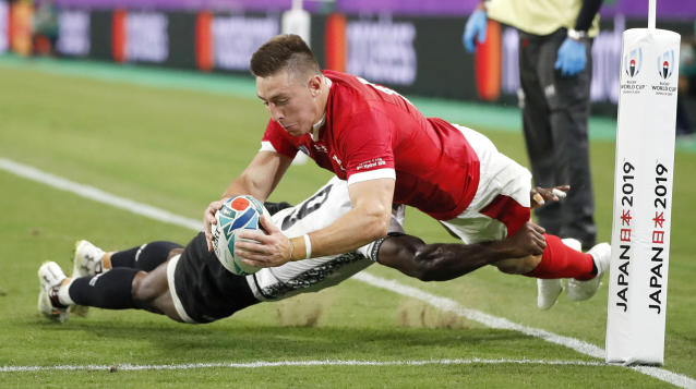 Wales' Josh Adams is tackled as he attempts to score a try during the Rugby World Cup Pool D game at Oita Stadium between Wales and Fiji in Oita, Japan, Wednesday, Oct. 9, 2019. (Kyodo News via AP)
