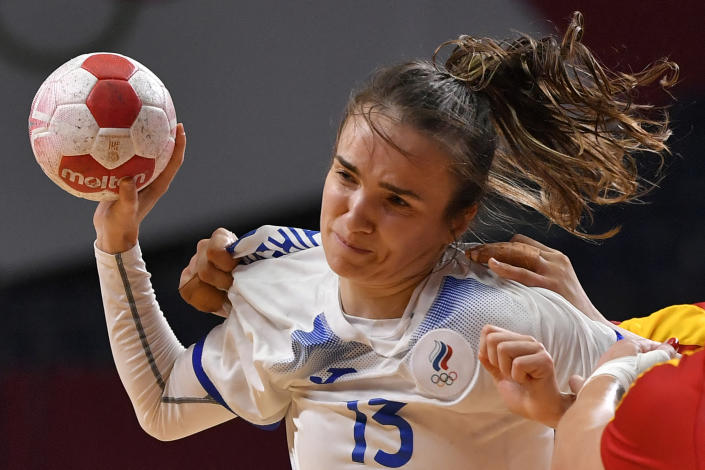 <p>Russia's right back Anna Vyakhireva is challenged during the women's quarterfinal handball match between Montenegro and Russia of the Tokyo 2020 Olympic Games at the Yoyogi National Stadium in Tokyo on August 4, 2021. (Photo by Fabrice COFFRINI / AFP)</p>