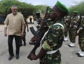FILE - In this Wednesday, July 20, 2011 file photo, the African Union envoy to Somalia, Jerry Rawlings, inspects a guard of honour of African Union peacekeepers, during a visit to displaced persons camps in southern Mogadishu, Somalia. Ghana's former president Jerry Rawlings, who staged two coups and later led the West African country's transition to a stable democracy, has died aged 73, according to the state's Radio Ghana and the president Thursday, Nov. 12, 2020. (AP Photo/Farah Abdi Warsameh, File)
