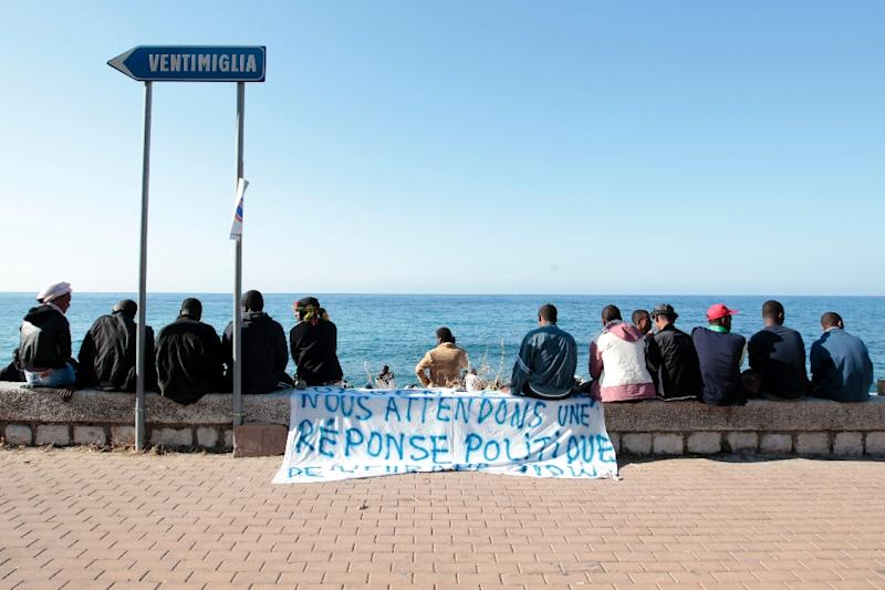 "Migrants sit near a banner reading ""We are waiting for a political response"" on the shores of the Mediterranean sea in Ventimiglia on June 15, 2015"