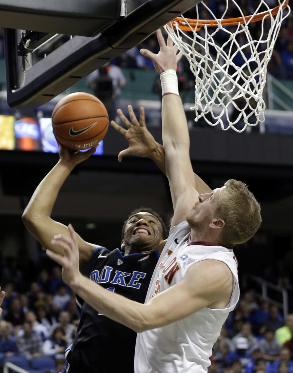 Duke's Jabari Parker, left, shoots over Elon's Lucas Troutman, right, during the first half of an NCAA college basketball game in Greensboro, N.C., Tuesday, Dec. 31, 2013. (AP Photo/Chuck Burton)