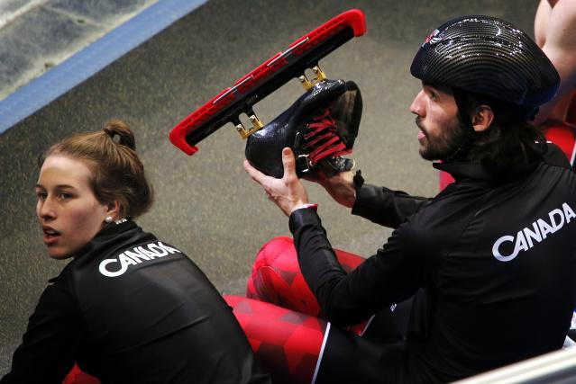 Canadian short track speed skater Hamelin takes off his skates beside St-Gelais after their training session in preparation for the 2014 Sochi Winter Olympics
