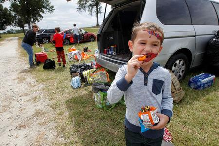 Five-year old Owen Hendon snacks as his family from Vero Beach, Florida begin packing up their car after sleeping in a tent and being offered a condo to sleep in to get away from Hurricane Irma at Atlanta Motor Speedway in Hampton, Georgia, U.S., September 10, 2017.  REUTERS/Tami Chappell