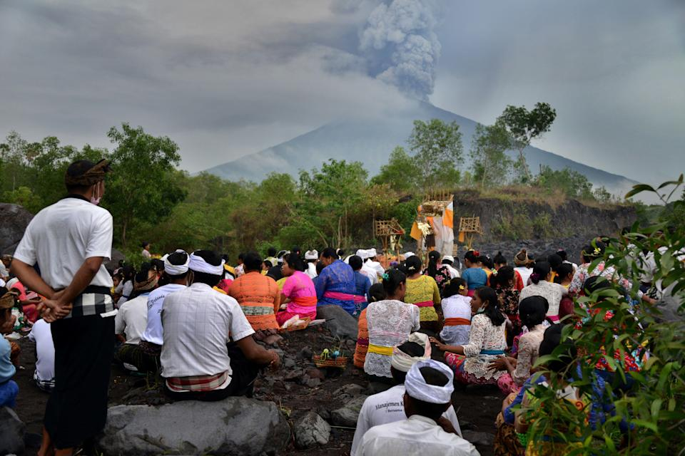 <p>Balinese Hindus take part in a ceremony, where they pray near Mount Agung in hope of preventing a volcanic eruption, in Muntig village of the Kubu sub-district in Karangasem Regency on Indonesia's resort island of Bali on Nov. 26, 2017. (Photo: Sonny Tumbelaka/AFP/Getty Images) </p>