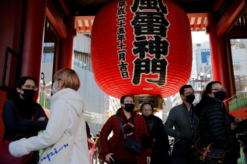 Tourists wearing face masks walk past Kaminarimon Gate as they visit Sensoji temple in Tokyo