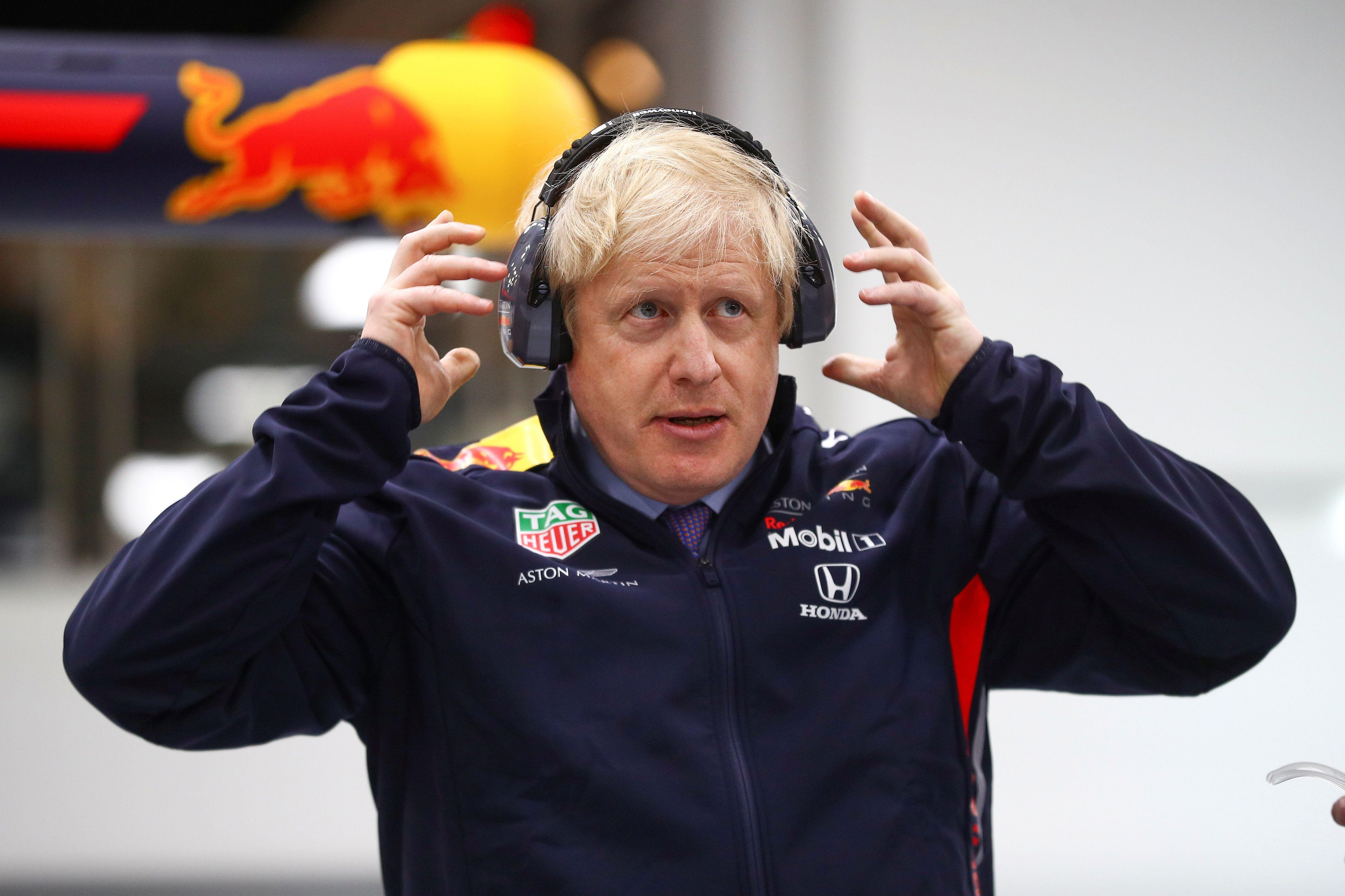 Britain's Prime Minister Boris Johnson dons protective safety wear as he prepares to change a wheel of a Formula One (F1) race car during a Conservative Party general election campaign visit to Red Bull Racing in Milton Keynes, north of London on December 4, 2019. - Britain will go to the polls on December 12, 2019 to vote in a pre-Christmas general election. (Photo by HANNAH MCKAY / POOL / AFP) (Photo by HANNAH MCKAY/POOL/AFP via Getty Images)