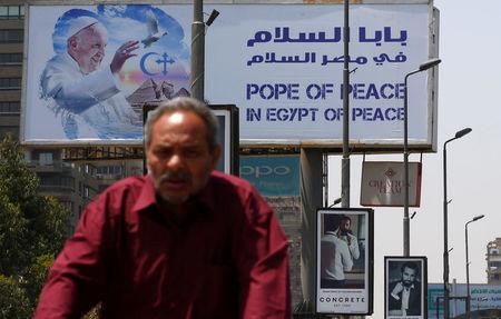 A man rides a bicycle past a billboard ahead of Pope Francis' visit in Cairo, Egypt April 26, 2017. REUTERS/Amr Abdallah Dalsh