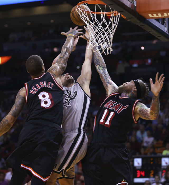 Miami Heat players Michael Beasley (8) and Chris Andersen (11) block San Antonio Spurs' Manu Ginbobil (20) during the first half of a NBA basketball game in Miami, Sunday, Jan. 26, 2014. (AP Photo/J Pat Carter)