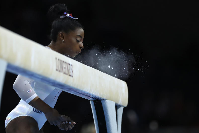Simone Biles of the United States blows the chalk from the balance beam before performing in the women's all-around final at the Gymnastics World Championships in Stuttgart, Germany, Thursday, Oct. 10, 2019. (AP Photo/Matthias Schrader)