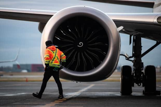 A worker walks past the engine of a Boeing 737 Max aircraft in Vancouver. Researchers say data on fly-in workers is hard to come by. Researchers say data about how may workers are in fly-in camps and what's happening within them should be publicly available.