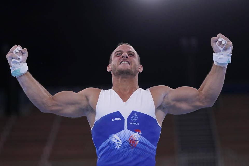 Samir Ait Said, of France, celebrates after performing on the rings during the men's artistic gymnastic qualifications at the 2020 Summer Olympics, Saturday, July 24, 2021, in Tokyo. (AP Photo/Gregory Bull)