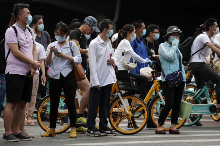 People wearing protective face masks to help curb the spread of the new coronavirus wait to cross a street in Beijing, Monday, June 22, 2020. A Beijing government spokesperson said the city has contained the momentum of a recent coronavirus outbreak that has infected a few hundreds of people, after the number of daily new cases fell to single digits. (AP Photo/Andy Wong)