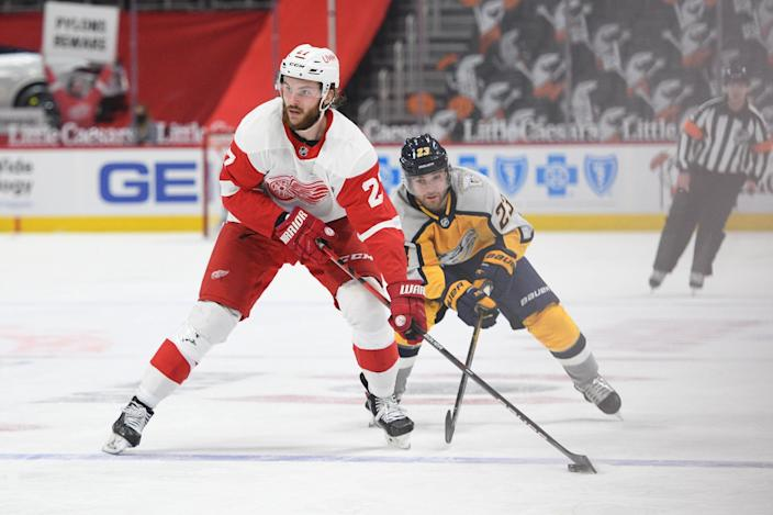 Detroit Red Wings center Michael Rasmussen (27) skates the puck up ice as Nashville Predators right wing Rocco Grimaldi (23) pursues during the second period April 6, 2021 at Little Caesars Arena.
