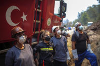 Turkish volunteers prepare to fight wildfires in Turgut village, near tourist resort of Marmaris, Mugla, Turkey, Wednesday, Aug. 4, 2021. As Turkish fire crews pressed ahead Tuesday with their weeklong battle against blazes tearing through forests and villages on the country's southern coast, President Recep Tayyip Erdogan's government faced increased criticism over its apparent poor response and inadequate preparedness for large-scale wildfires.(AP Photo/Emre Tazegul)