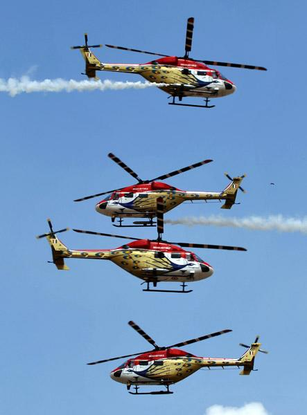 The Indian Air Force Sarang aerobatics team perform in their HAL Dhruv helicopters during Aero India 2013 at the Yelahanka Air Force station in Bangalore on February 6, 2013. India, the world's leading importer of weaponry, opened one of Asia's biggest aviation trade shows Wednesday with Western suppliers eyeing lucrative deals and a Chinese delegation attending for the first time. AFP PHOTO/Manjunath KIRAN