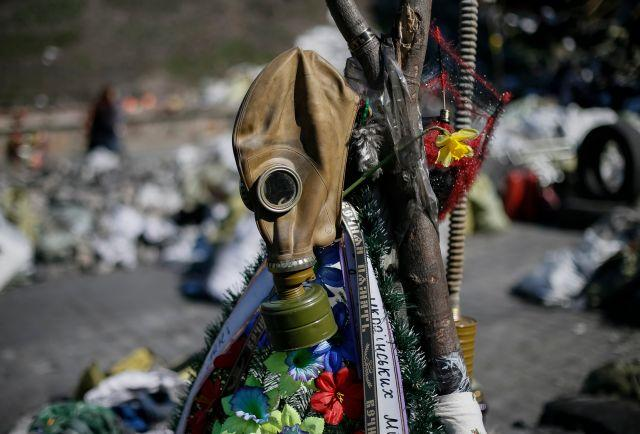 A gas mask and flowers are seen at the site of the recent clashes in Kiev March 30, 2014.