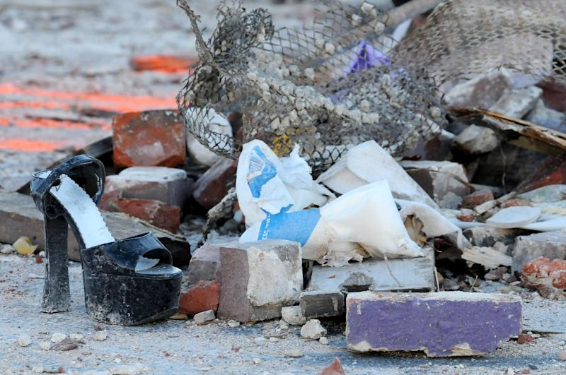Items from the Score's Gentleman's Club are seen in the rubble on Saturday, Nov. 24, 2012, the morning after Friday night's explosion in Springfield, Mass. Dozens of building inspectors began assessing homes and businesses in Springfield on Saturday, a day after a natural gas explosion leveled the Scores Gentleman's Club located next to a day care and heavily damaged a dozen other structures. (AP Photo/The Republican, Dave Roback)