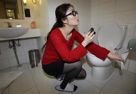 Ms. Zhuang, a Hotel Test Sleeper, checks the texture of the toilet paper at a business chain hotel, in Beijing March 6, 2012. The requirement for this new profession is to sleep at selected hotels without disclosing their real job and write expert reviews about the facilities, location, dining, services and prices of the hotels, in order to provide an independent third-party evaluation and an authoritative guide to travelers, according to the company.