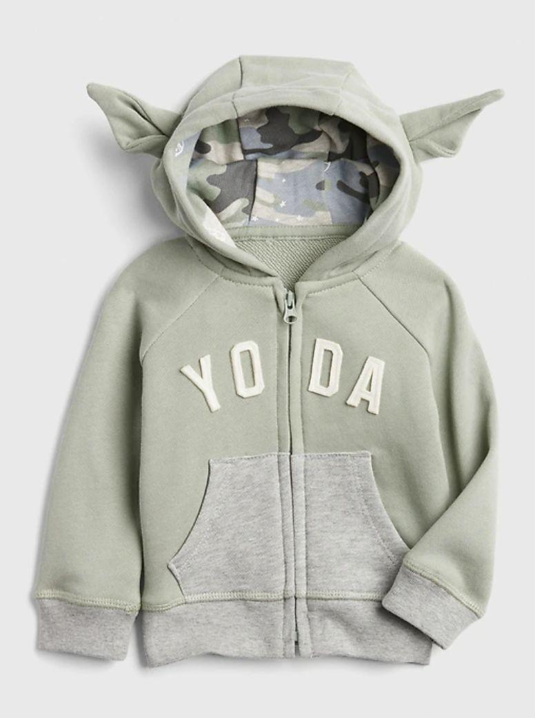 """You can't forget about the little ones. This hoodie is meant for those who are only a couple of months old to two-year-olds. Now, they can actually be a <i>baby</i> Yoda, with a hood that features those famous ears.<a href=""""https://fave.co/3fSL8Qw"""" target=""""_blank"""" rel=""""noopener noreferrer"""">Find it for $40 at Gap</a>."""