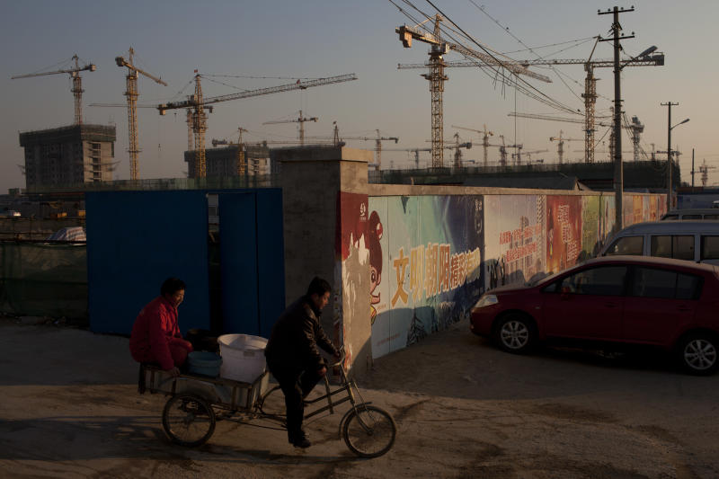 In this Jan. 17, 2013 photo, workers ride a tricycle outside a construction site of a residential real estate project in Beijing, China. China's economy rebounded in the final quarter of 2012 but optimism was tempered by warnings the shaky recovery could be vulnerable to a possible downturn in global trade. (AP Photo/Alexander F. Yuan)