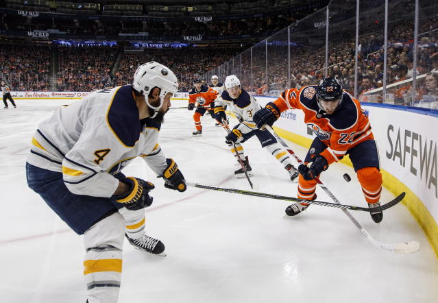 Buffalo Sabres' Zach Bogosian (4) and Edmonton Oilers' Tobias Rieder (22) battle for the puck during second period NHL hockey action in Edmonton, Alberta, on Monday, Jan. 14, 2019. (Jason Franson/The Canadian Press via AP)