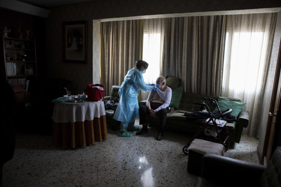 Nurse Pilar Rodríguez administers the COVID-19 vaccine to Rafael Capo Frau, 92, at his home in the town of Sa Pobla on the Spanish Balearic Island of Mallorca, Spain, Friday, April 30, 2021. Over a million Spaniards are considered by social services to be in need of help to feed and care for themselves. Some of these people are homebound and cannot respond to calls to go to vaccination points when their turn comes up. (AP Photo/Francisco Ubilla)