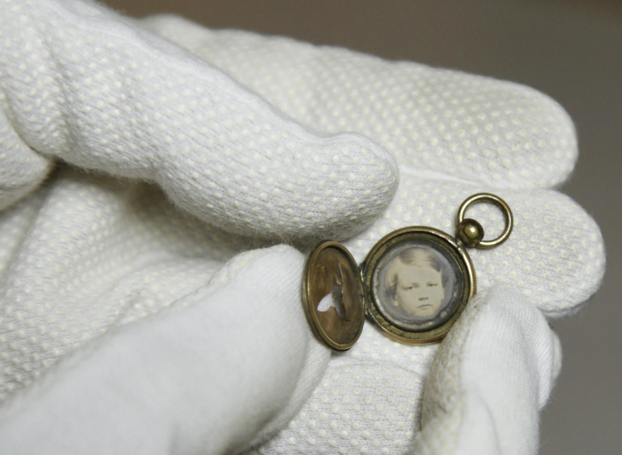 Ann Drury Wellford, manager of Photographic Services for The Museum of the Confederacy, holds a Civil War battlefield photo at the museum in Richmond, Va., Friday, May 25, 2012. This Gem daguerreotype locket was found by a soldier in Hampton's cavalry brigade on a battlefield in 1863. Eight photographs are publicly releasing the images in the admittedly remote chance a descendant might recognize a facial resemblance or make a connection the battlefields where they were found. (AP Photo/Steve Helber)
