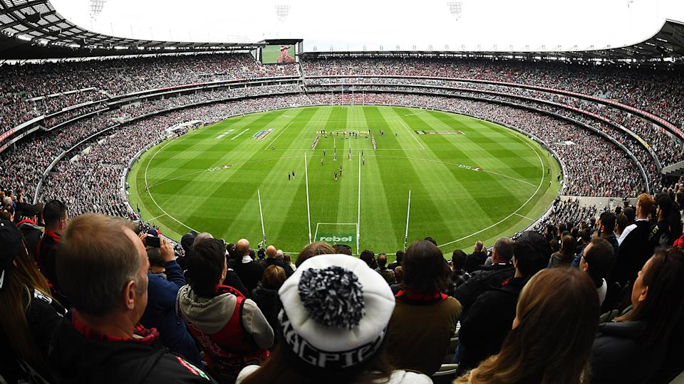 The crowd, pictured here standing for the Last Post during the Anzac Day clash between Collingwood and Essendon.
