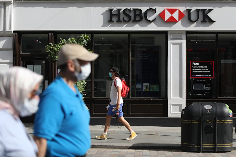 People wearing face covering pass a HSBC UK branch near Covent Garden in London, as the bank has announced to accelerate plans to cut 35,000 jobs globally after the Covid-19 crisis forced the bank to put aside another $3.8bn (�2.9bn) to cover bad debts. Picture date: Friday August 7, 2020.