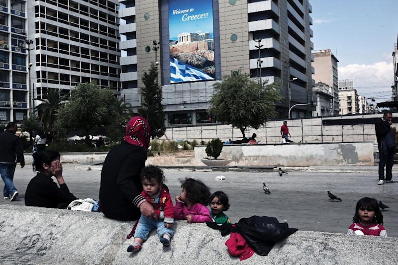 Syrian migrants who arrived in Greece by its sea borders, sit on Omonia Square in Athens on April 25, 2015