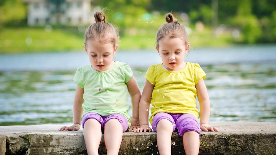 two identical twin girls sitting on a log with their feet in the water