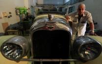 """Sayed Sima, a 70-years-old Egyptian collector of vintage car, stands next to a 120-year-old American """"1900 Auburn"""" automobile in his store, the Giza suburb of Abu Rawash"""