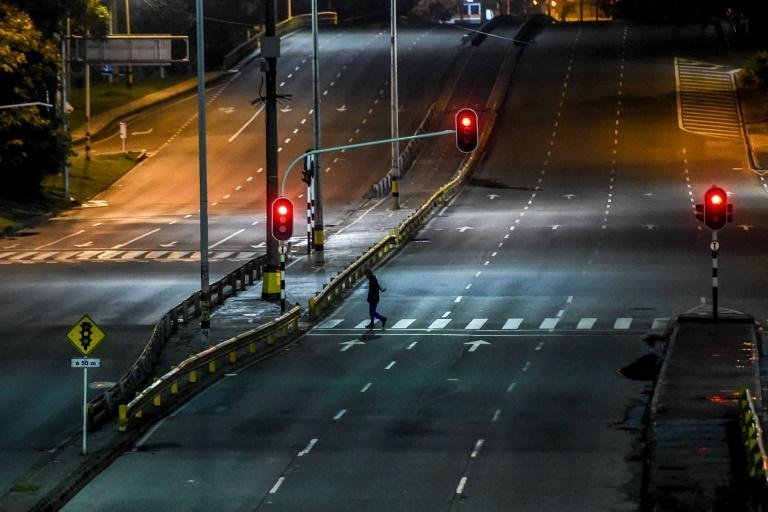 A man crosses an empty avenue in Medellin, Colombia, on January 7, 2021 as authorities placed several regions under a new lockdown after an increase in coronavirus cases