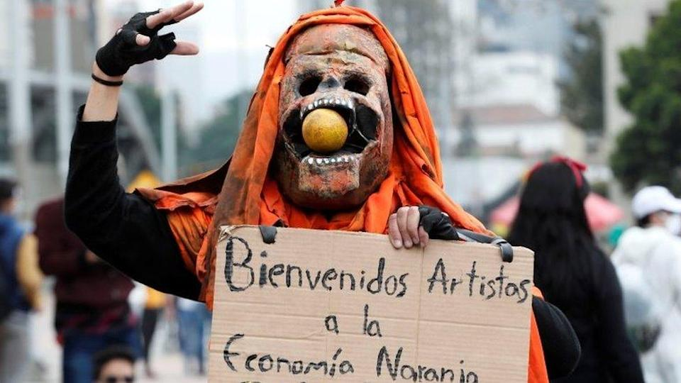 """A person in a costume carries a poster against the so-called """"Orange Economy"""""""