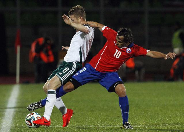 Chile's Jorge Valdivia, right, battles for the ball with Northern Ireland's Steven Davis, during an international friendly soccer match in Valparaiso, Chile, Wednesday, June 4, 2014. (AP Photo/Luis Hidalgo)