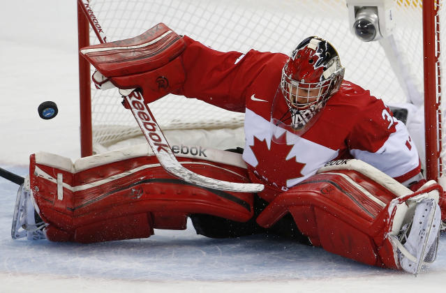 Goalkeeper Charline Labonte of Canada bats the the puck away during the 2014 Winter Olympics women's ice hockey game against the United States at Shayba Arena, Wednesday, Feb. 12, 2014, in Sochi, Russia. (AP Photo/Petr David Josek)