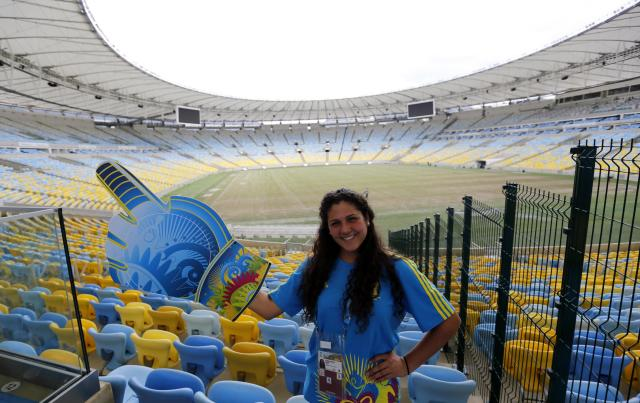 A volunteer poses for a picture inside the Maracana stadium, one of the stadiums hosting the 2014 World Cup soccer matches, during a press visit in Rio de Janeiro, May 26, 2014. REUTERS/Sergio Moraes (BRAZIL - Tags: SPORT SOCCER WORLD CUP)