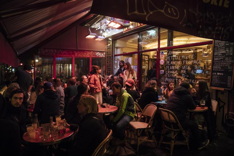 People enjoy a drink on a bar terrace in Paris, Monday, Oct. 5, 2020.