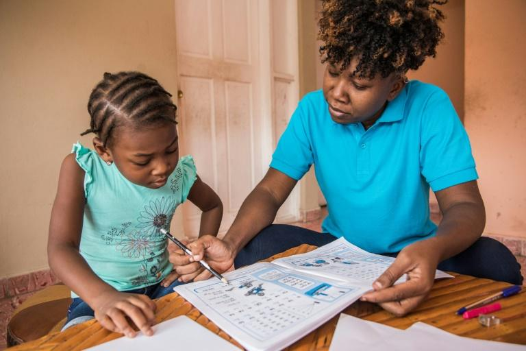 Edine Celestin (R) is homeschooling her five-year-old daughter Lyne-Renee as schools have been closed in Haiti's capital Port-au-Prince because of political unrest