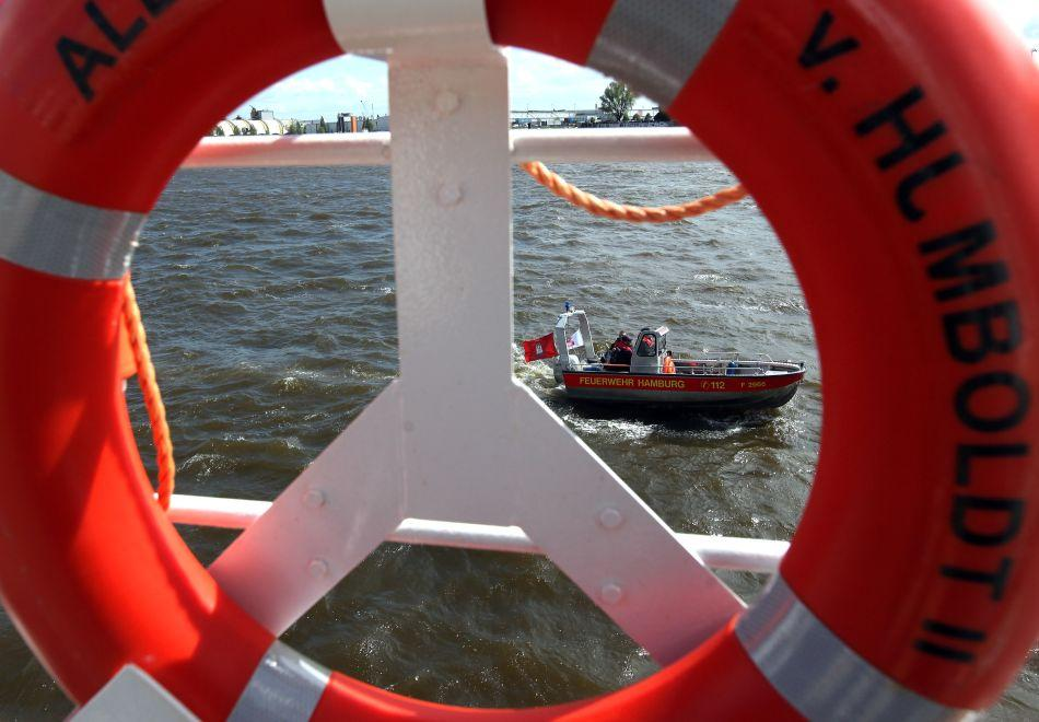 A fire department rescue boat is seen through a life preserver of the German ship Alexander von Humboldt II.