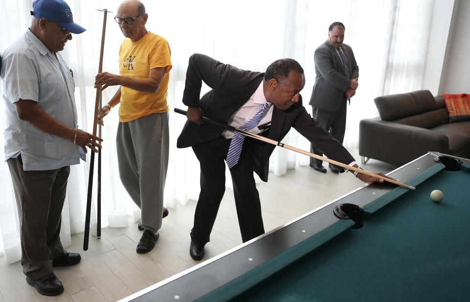 Housing and Urban Development Secretary Ben Carson takes a shot on the pool table as he visits Colllins Park apartment complex on April 12, 2017 in Miami, Florida. (Photo: Joe Raedle/Getty Images)
