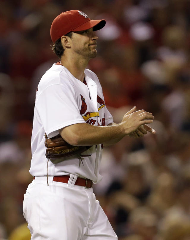 St. Louis Cardinals starting pitcher Adam Wainwright rubs up a new ball as he walks back to the mound after giving up a ground-rule double to Milwaukee Brewers' Ryan Braun during the fifth inning of a baseball game Friday, Aug. 1, 2014, in St. Louis. Carlos Gomez scored on the play. (AP Photo/Jeff Roberson)