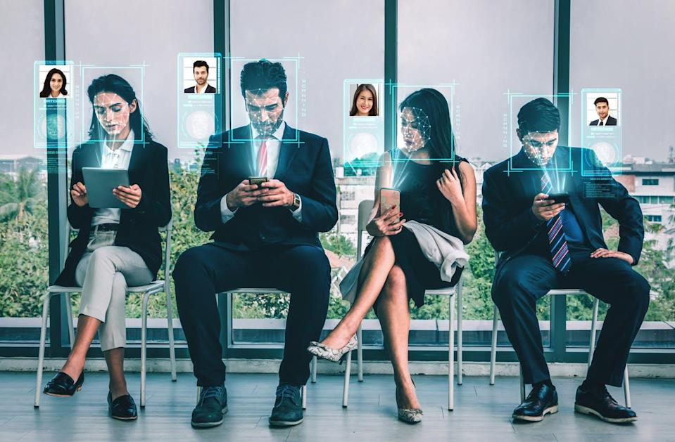 A row of four people in business attire on their mobile phones. Holograms of profile pictures float above them