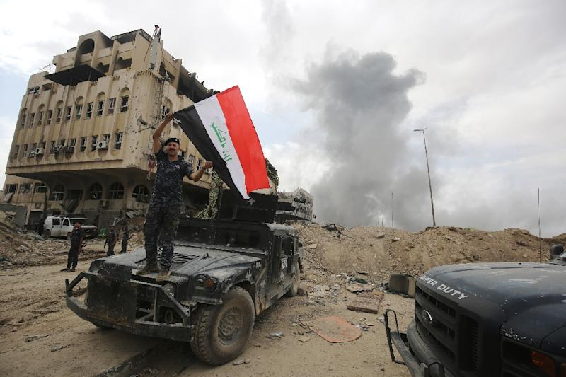 A member of the Iraqi federal police waves the national flag in the Old City of Mosul on July 8, 2017
