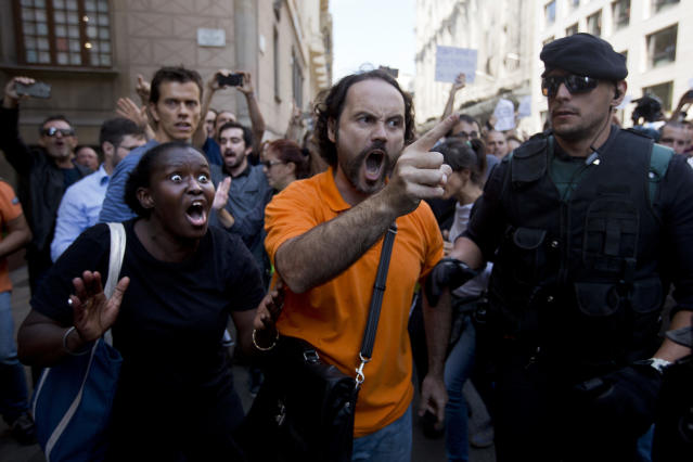 <p>Demonstrators react as they try to stop the car carrying Xavier Puig, a senior at the Department of External Affairs, Institutional Relations and Transparency of the Catalan Government office, after he was arrested by Guardia Civil officers in Barcelona, Spain, Wednesday, Sept. 20, 2017. (Photo: Emilio Morenatti/AP) </p>