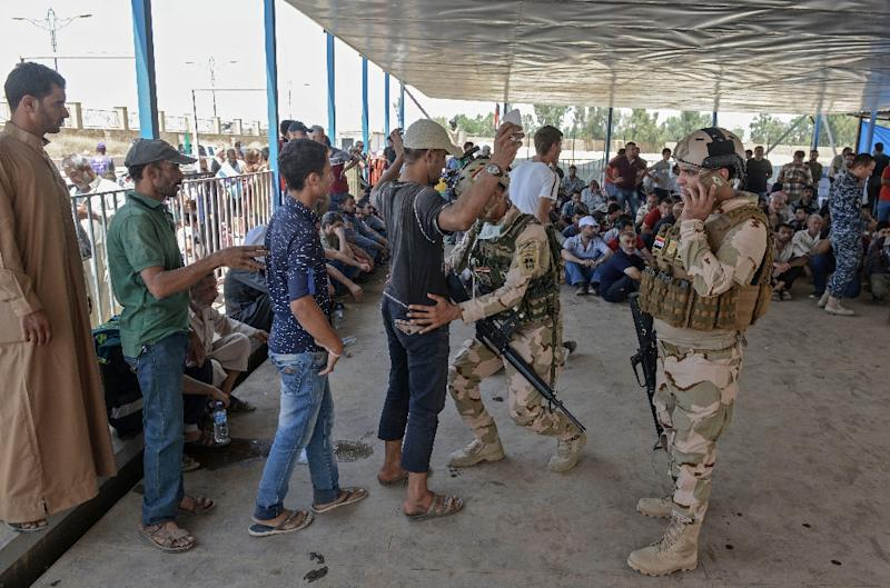 An Iraqi soldier frisks a displaced Iraqi man at a temporary camp in the compound of a hotel in Mosul on June 16, 2017 (AFP Photo/MOHAMED EL-SHAHED)