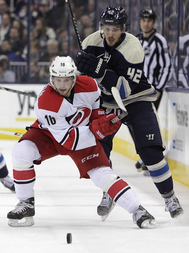 Carolina Hurricanes' Elias Lindholm, front, of Sweden, clears the puck as Columbus Blue Jackets' Artem Anisimov, of Russia, defends during the second period of an NHL hockey game on Friday, Jan. 10, 2014, in Columbus, Ohio. (AP Photo/Jay LaPrete)